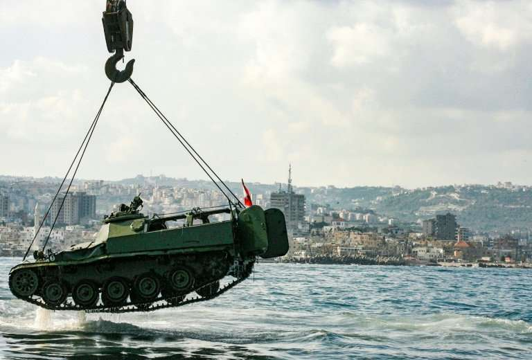 Environmental activists drop off an old mechanised armoured personnel carrier provided by the Lebanese Armed Forces into the Med