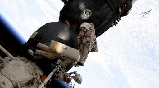 Spacewalking astronauts check site of capsule leak