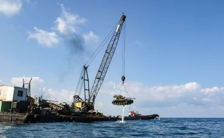 Environmental activists drop off an old battle tank provided by the Lebanese Armed Forces into the Mediterranean Sea, about thre