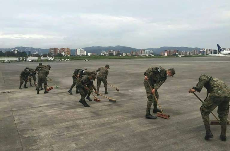 A handout picture released by the Guatemalan National Army shows soldiers at the International airport in Guatemala City cleanin