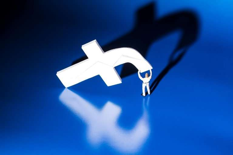 This file photo taken on May 16, 2018 shows a figurine carrying the logo of social network Facebook in Paris