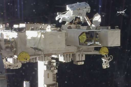 Spacewalking astronauts set up TV cameras for arriving ships