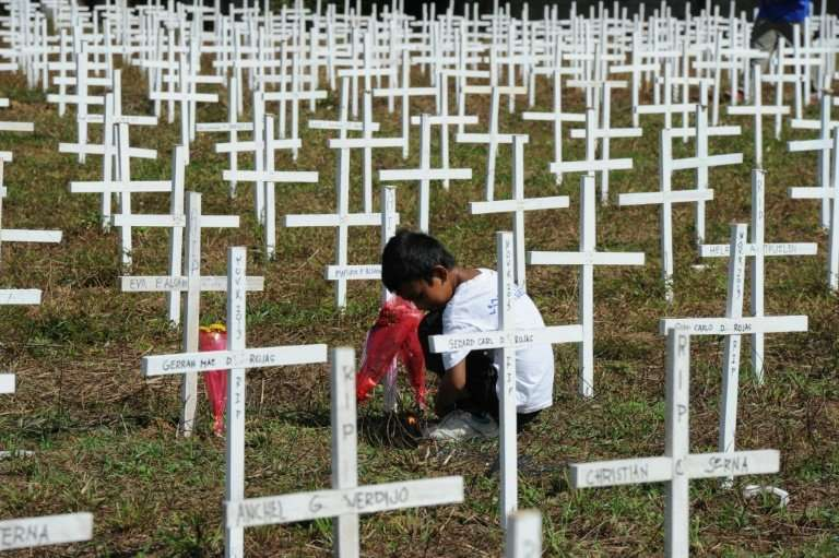 A boy sits next to wooden crosses during a memorial ceremony marking the first anniversary of Super Typhoon Haiyan at a mass gra