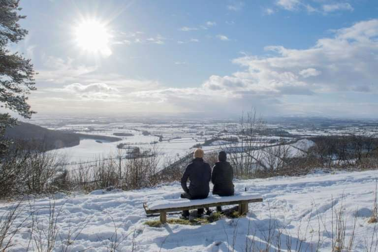 A couple sit on a bench overlooking the snow-covered fields of Thirsk in the North Yorks Moors National Park in North Yorkshire,