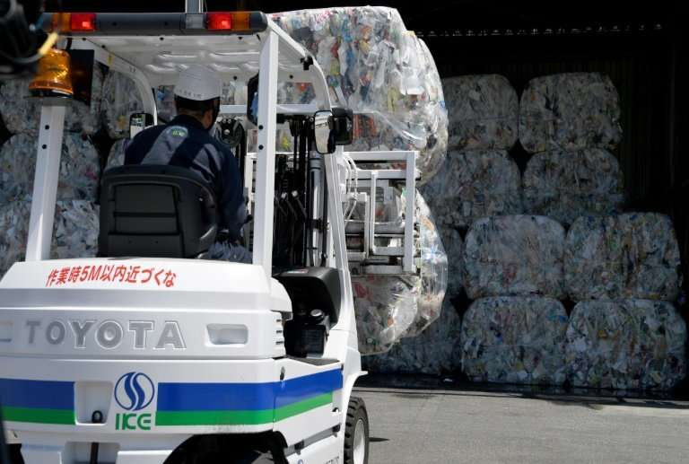 A forklift moves compressed bales of plastic at a recycling plant outside Tokyo
