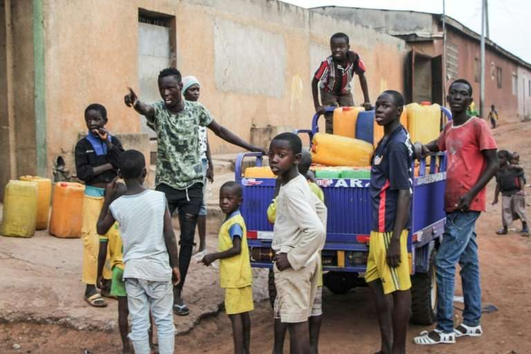 After three weeks of dry taps in a time of drought, residents queue for well water in Ivory Cast's second city, Bouake