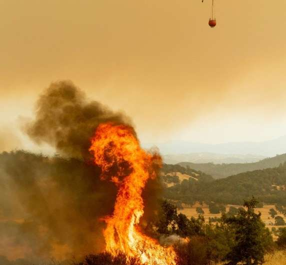A helicopter prepares to drop water on the Ranch Fire, part of the Mendocino Complex Fire, burning on High Valley Rd. near Clear