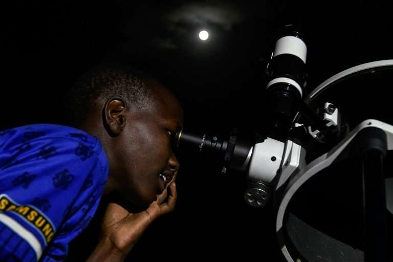 A man looks through a telescope set up to let the local community at Lake Magadi in Kenya watch the lunar eclipse on Friday