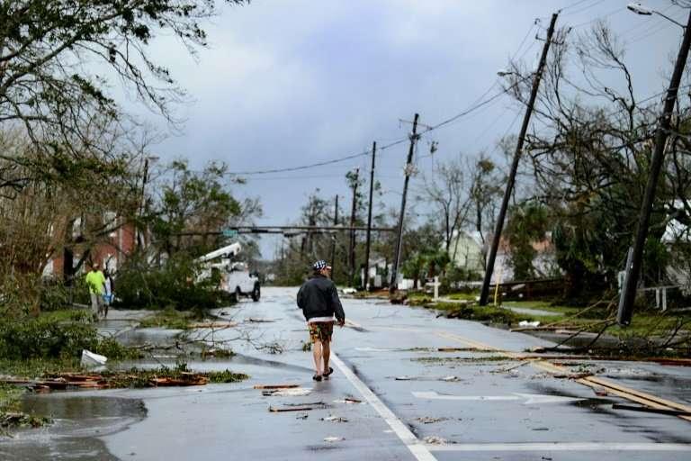 A man walks down a street after Hurricane Michael hit Panama City, Florida