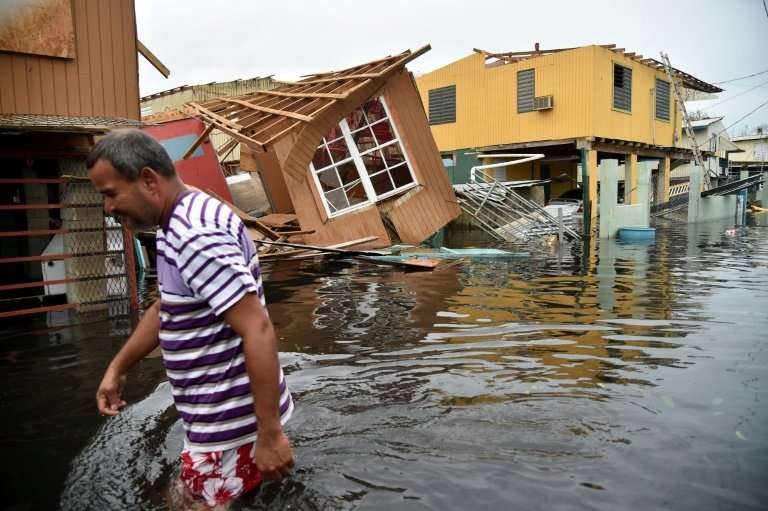 A man walks past destroyed homes in Catano, Puerto Rico, on September 21, 2017 in the wake of Hurricane Maria