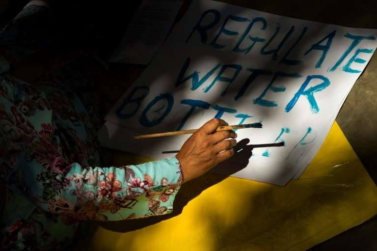 A man writes on a placard before taking part in a protest against the way the Cape Town city council has dealt with the water sh