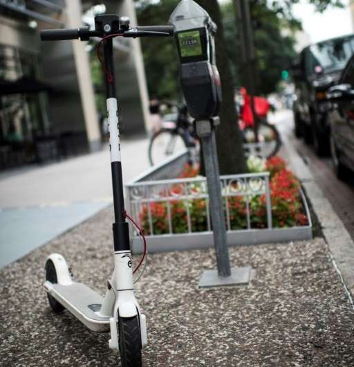An electric scooter belonging to the startup Bird waits for a rider on a street of downtown Washington, DC