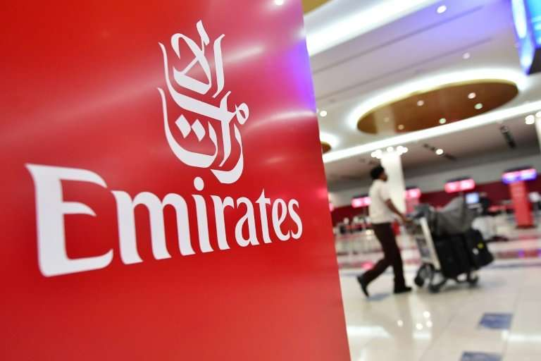 A passenger walks past an Emirates Airline logo at Dubai International Airport on October 10, 2018