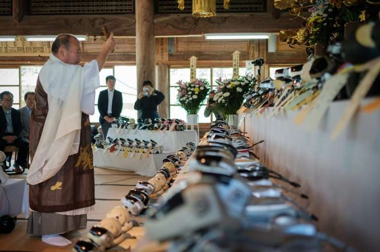 A priest offers a prayer for Sony's pet robot AIBOs displayed on an altar prior to hold the robots' funeral at the Kofukuji temp