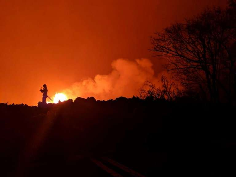 A scientist from the US Geological Survey examines a fissure from the Kilauea volcano in Hawaii