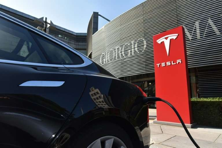 A Tesla car charges at a charging station outside a shopping mall in Beijing in September 2017