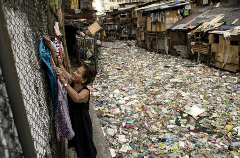 A thick layer of garbage lies atop a creek flowing between the makeshift homes of a Manila slum