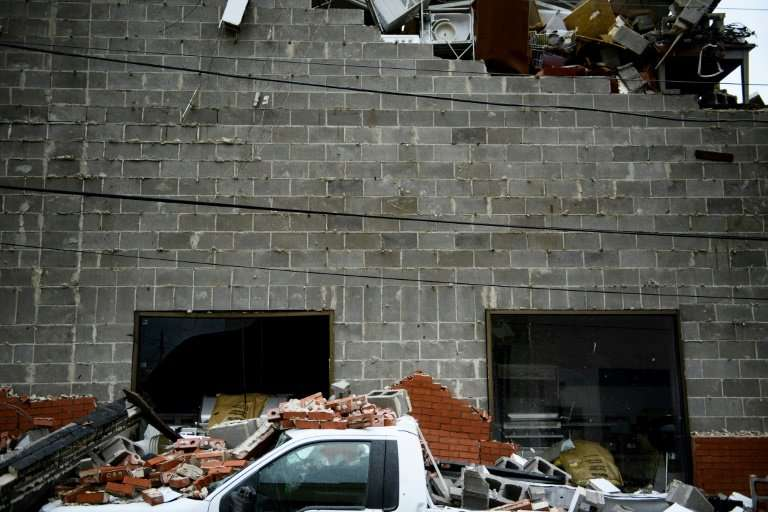 A truck is seen below a partially collapsed wall damaged by Hurricane Michael in Panama City, Florida