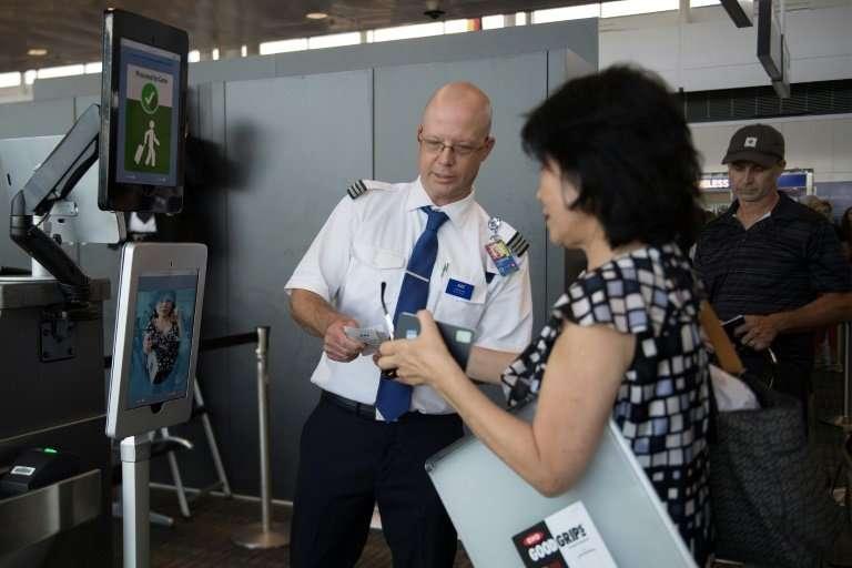 A woman boarding an SAS flight to Copenhagen goes through a facial recognition verification system at Dulles International Airpo