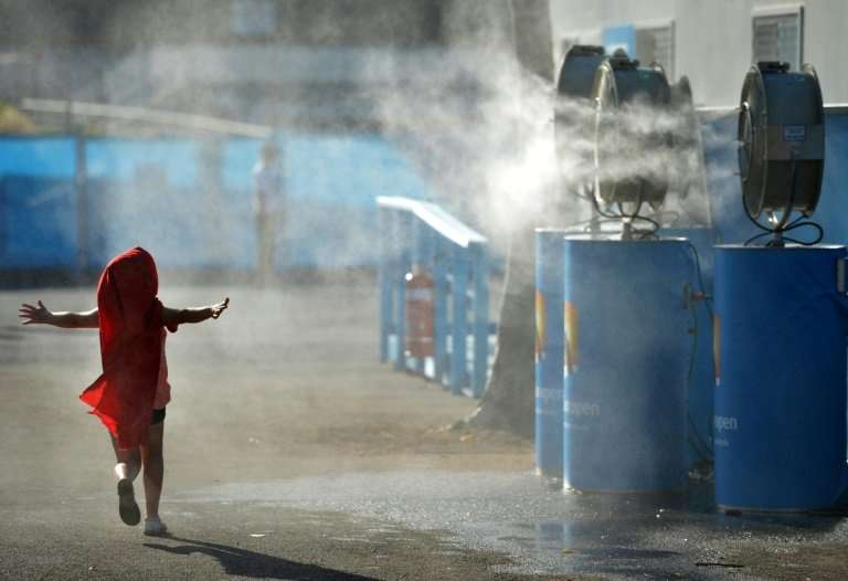 A young child cools off by running past a set of vapour fans in Melbourne