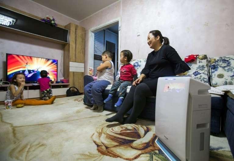 Batbayariin Munguntuul sitting with her children while an air purifier runs at her home in Ulaanbaatar