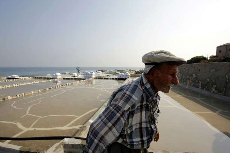 Elias al-Najar, 93, walks past a salt evaporation pond in the coastal Lebanese town of Anfeh on July 21, 2017