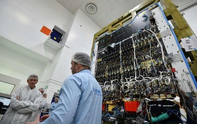 ESA astronaut Tim Peake (L) listens to a technician in the cleanroom explaining details about the Eutelsat Quantum satellite, bi