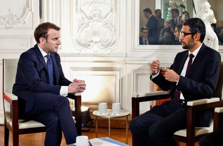 "French President Emmanuel Macron (L) talks with Google CEO Sundar Pichai during the ""Choose France"" summit at the Chat"