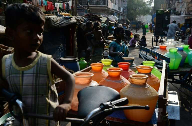 Indian residents carry plastic pots with drinking water in a supply cart from a government water supply tanker at their resident