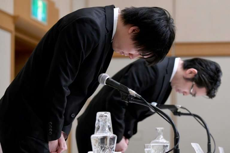 Koichiro Wada (left), Coincheck president, and chief operating officer Yusuke Otsuka, bow at the beginning of a press conference