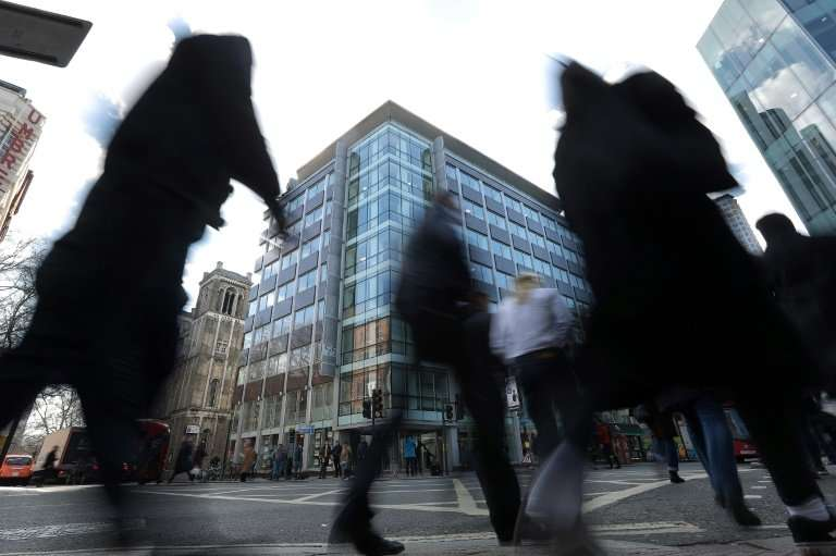 Pedestrians pass the shared building which houses the offices of Cambridge Analytica in central London on March 21, 2018