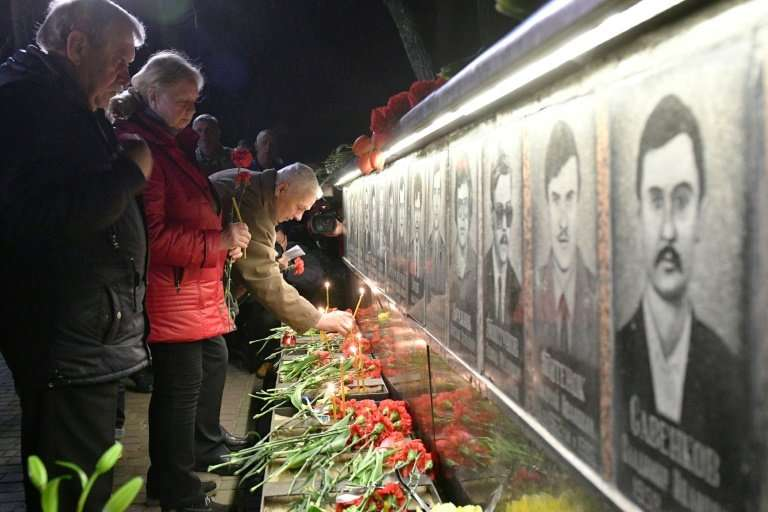 People light candles and place flowers at the monument for victims in Slavutich, some 50 kms from the accident site