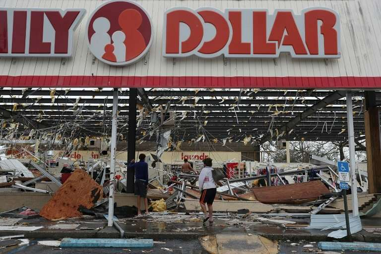 People look at a damaged store after Hurricane Michael ripped through Panama City, Florida