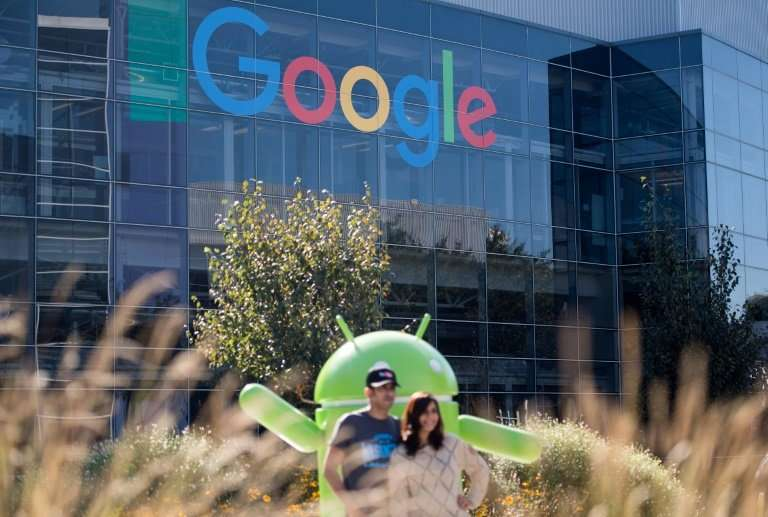 People pose for a picture near a Google sign and Android statue at the tech giant's California Googleplex in 2016