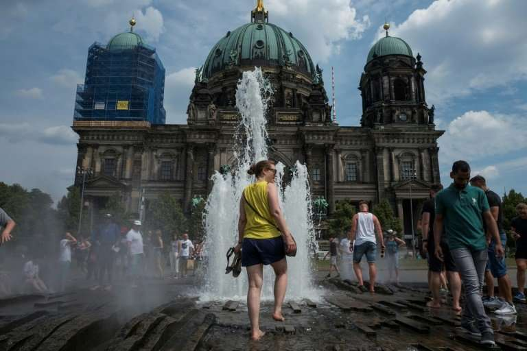 People walk in a fountain in front of the Berlin Cathedral as the heatwave in Europe continues
