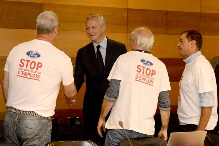"""""""Stop job cuts"""" read the T-shirts of trade unionists greeting French Economy and Finance Minister Bruno Le Maire at a"""