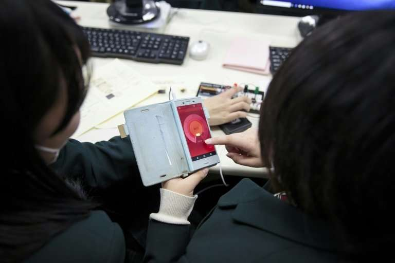 Schoolgirls check an app connected to a geiger counter to measure radiation in a classroom in Fukushima prefecture