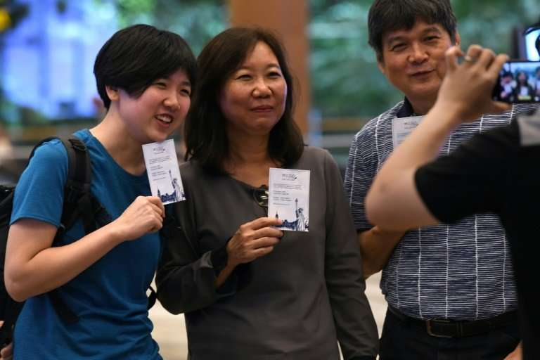 Singaporean William Chua (R) with family members, all passengers of flight SQ22, Singapore Airlines' inaugural non-stop flight t