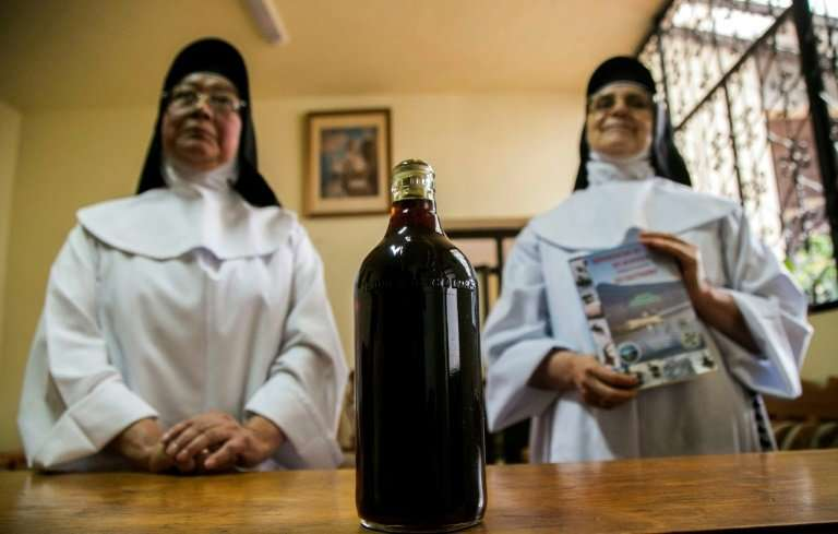 Sisters Ofelia Morales Francisco (L) and Rosa Cortez are shown next to a bottle of achoque (Ambystoma dumerilii) syrup produced