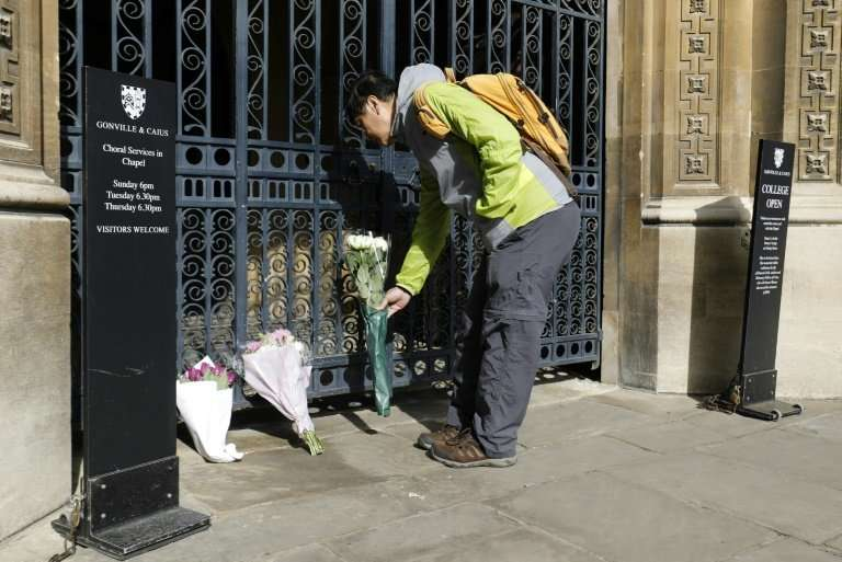 Well-wishers such as this man laying flowers outside Gonville and Caius College, Cambridge, where Stephen Hawking worked  to unl