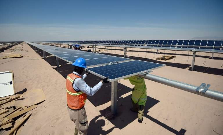 Workers install new solar panels at a power plant in the desert near Villanueva, Mexico, taken on April 20, 2018