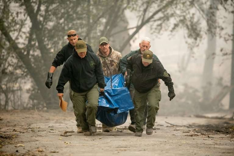 Yuba County Sheriff officers carry a body away from a burned residence in Paradise, California