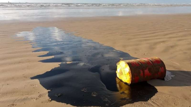 A barrel of oil leaking on a beach in Barra dos Coqueiros, in the Braziilian state of Sergipe