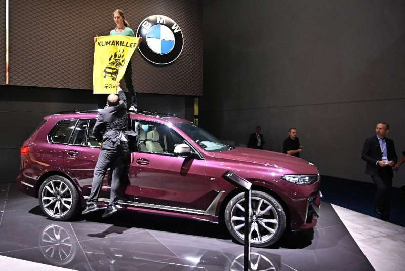 A Greenpeace activist protested at the Frankfort motor show earlier this week by standing on top of a SUV on display with a post