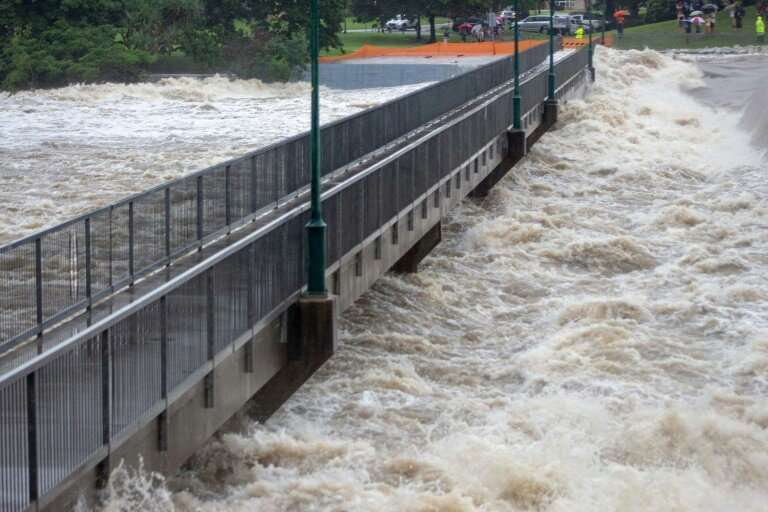 A handout picture provided by the Queensland Fire and Emergency Services shows floodwaters as they rush over the Aplins Weir in