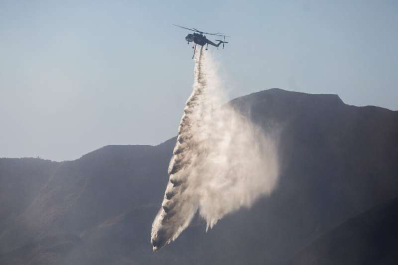 A helicopter drops water on the Maria Fire in Santa Paula, California on November 01, 2019