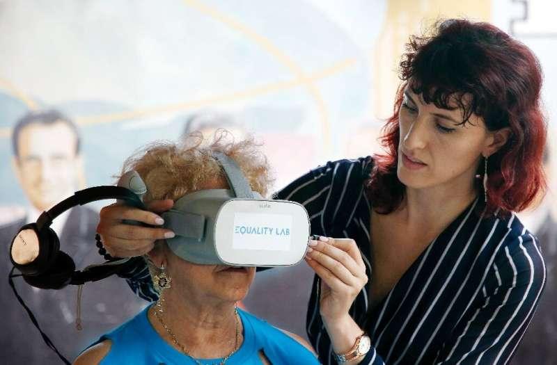 Alexandra Ivanovitch (R) assists Nidia Silva (L) with the virtual reality headset in the Little Havana neighborhood of Miami, Fl