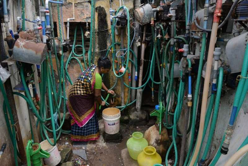 An Indian resident fills a bucket with water from a tap at a residential complex in Chennai on June 26, 2019
