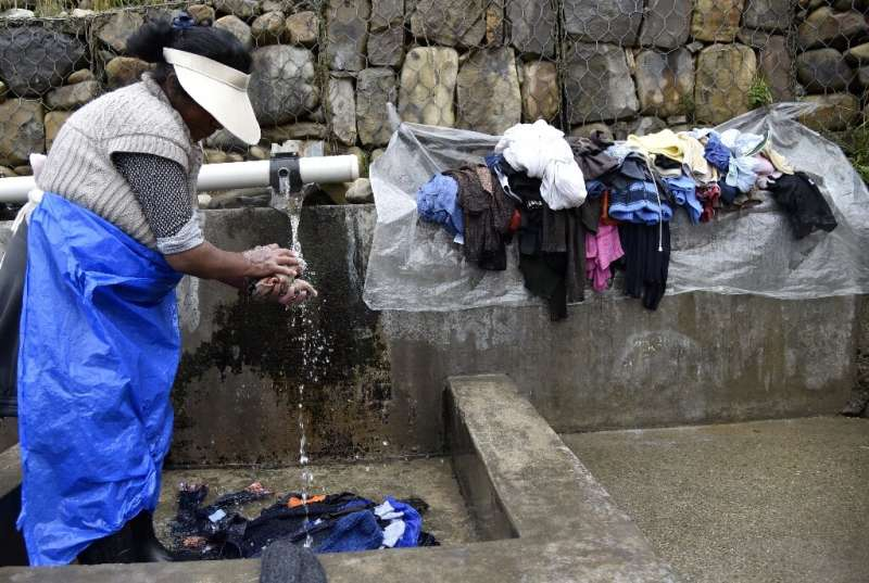 A woman washes clothes at a municipal laundry, which uses spring water to conserve the public distribution system's water, in La
