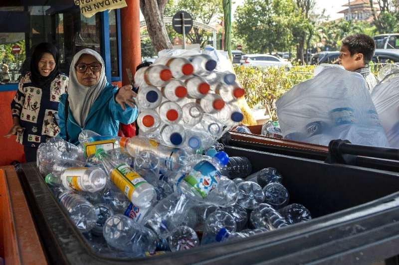 Dozens of people clutching bags full of plastic bottles and disposable cups queue at a busy bus terminal in the Indonesian city